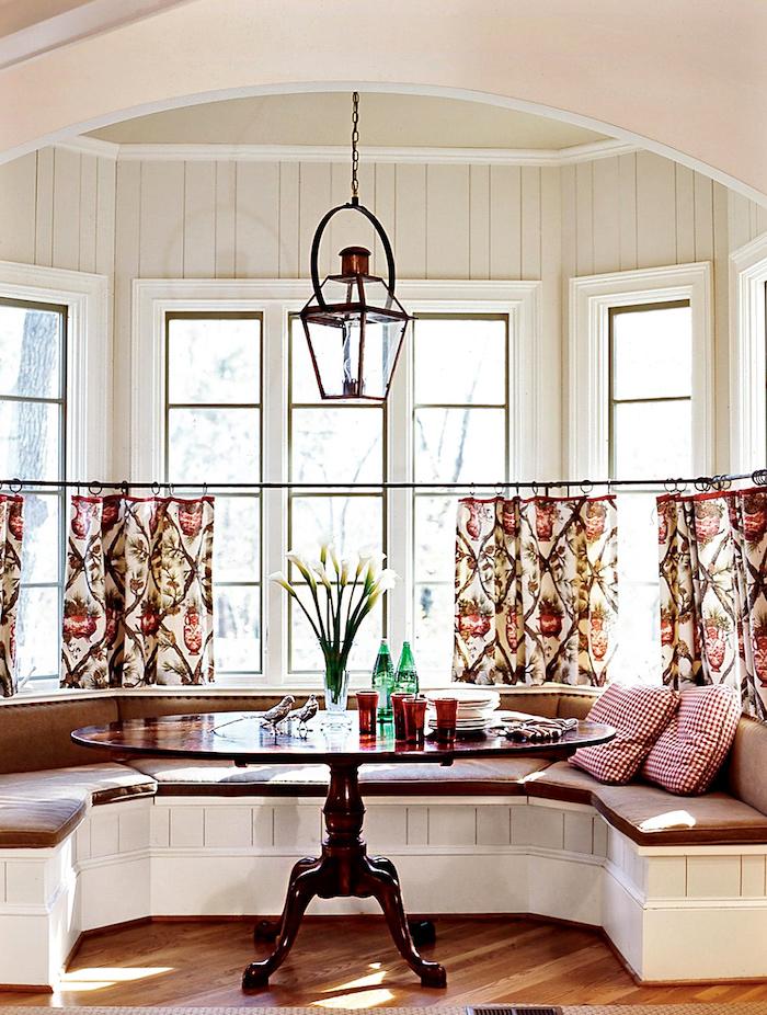 table et banquettes rondes dans un coin repas de cuisine avec deux bouteilles d eau et une vase a fleurs sur la table