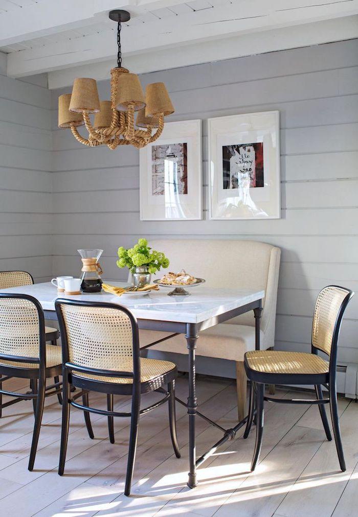 table plan de travail avec des chaises autour et un petit canape en cuir blanc murs et sols en pailles et deux tableaux