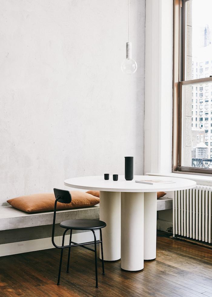 table plan de travail pres de la fenetre a cote d un banc avec coussins et une petite chiaise noir