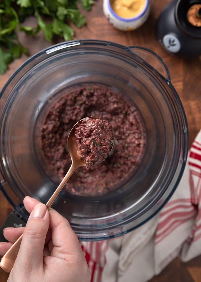 tartine salee a la base d olives mixture dans un robot de cuisine avec une cuillere bronzee
