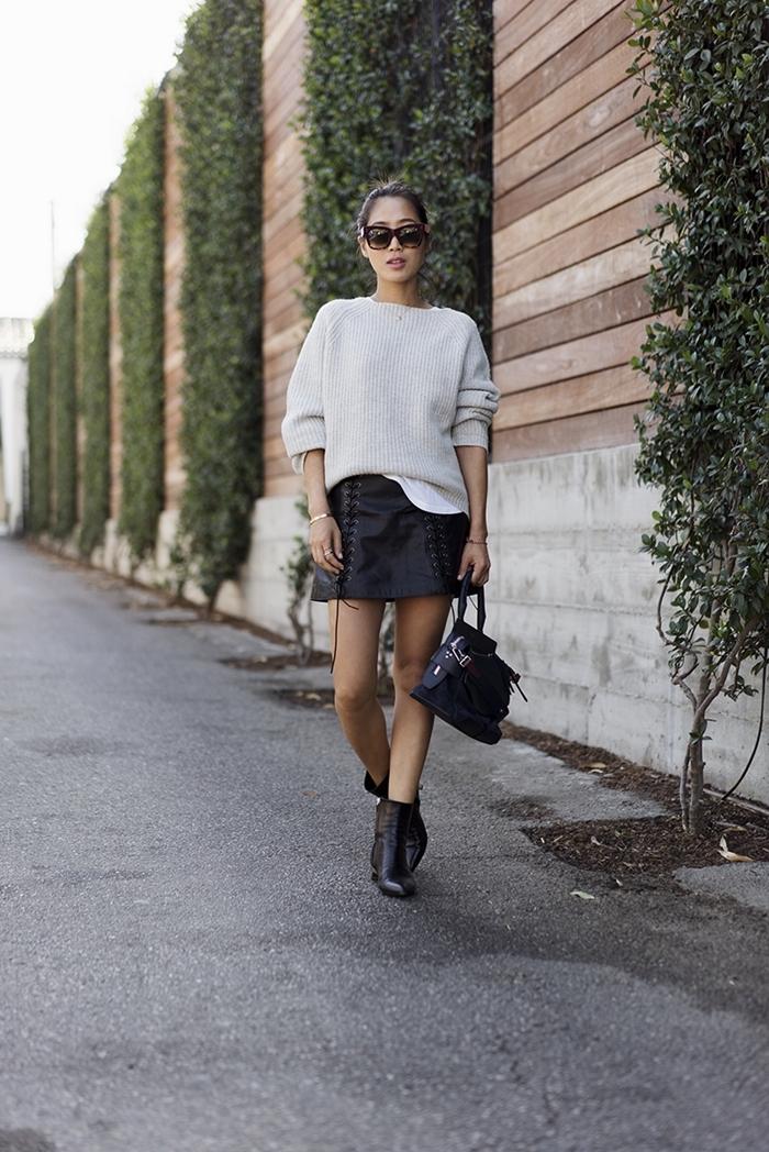 tenue automne femme bottines avec jupe courte noire pull blanc lunettes de soleil sac à main cuir noir bracelet or