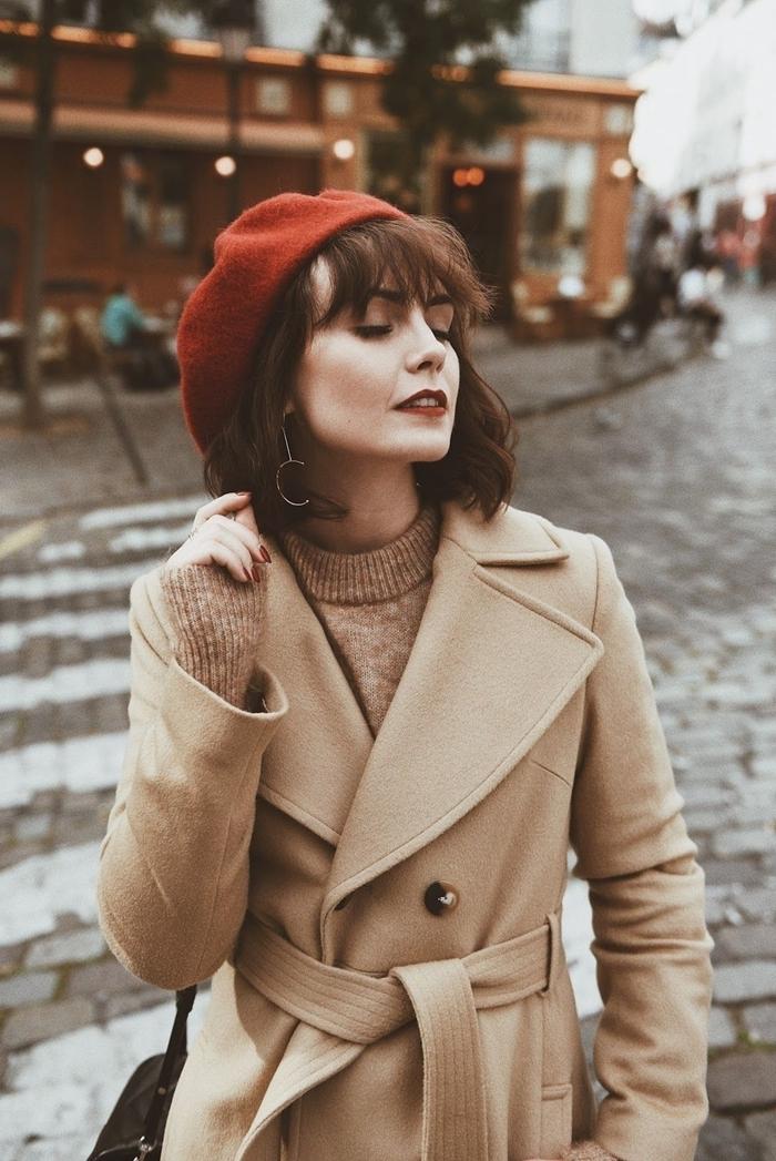 tenue femme hiver béret marron coupe avec frange boucles d oreilles or pull over robe beige manteau ceinture boutons