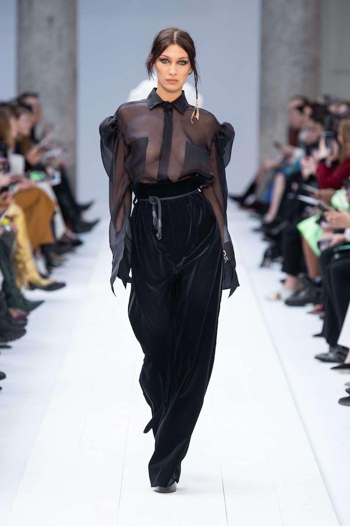tenue hiver femme bella hadid en chemisier transparent et un patnalon taille haure noir des cheveux en queue