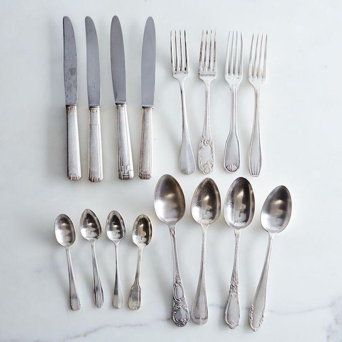 un ensemble de couverts argentines des cuilleres couteaux fourchettes sur une surface blanche comment mettre la table