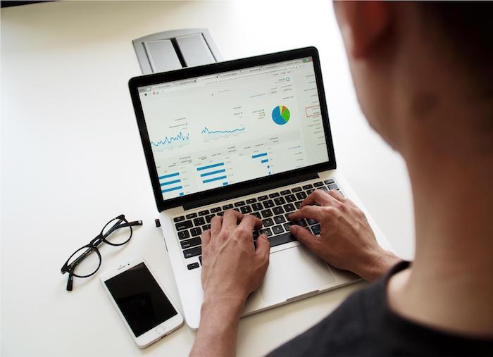 un homme qui fait une recherche sur intenet des lunettes un portable et un ordinateur sur le bureau