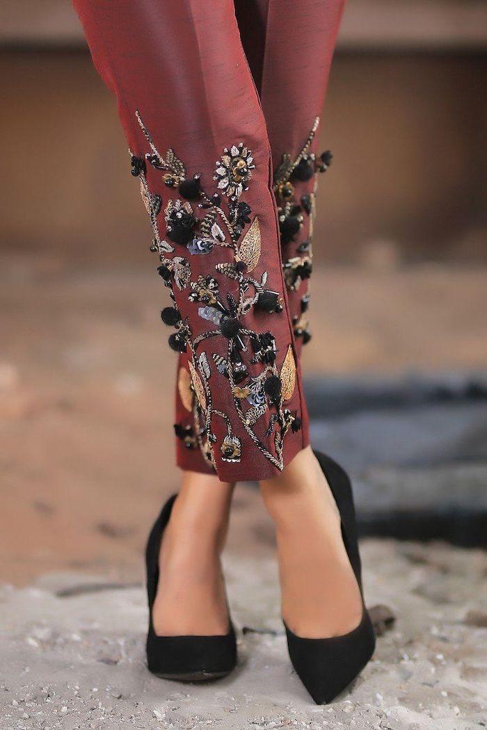 un pantalon couleur brodeaux customise avec des broderies et des pailettes coudes autour les chevilles