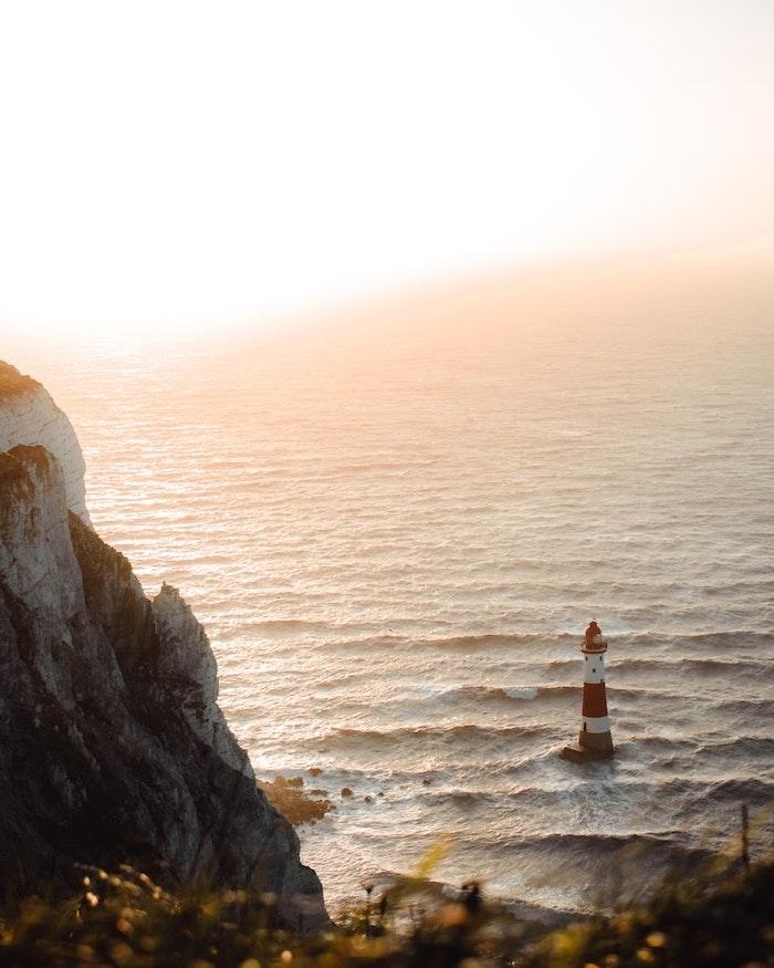 un phare dans la mer une roche jonche et le soleil a l horizont fond d ecran pale