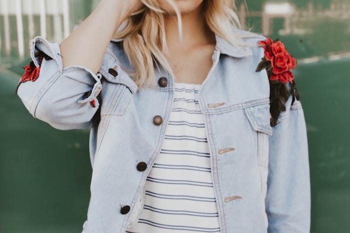 une femme en top blanc raye et une veste en jean customise avec une fleur brode sur l epaule