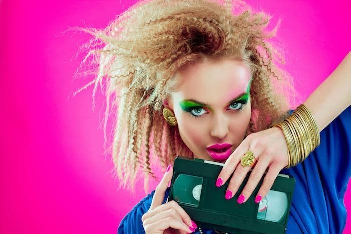 une fille recreation du style années 80s cheveux blondes en cheveux gauffrés casette vhs
