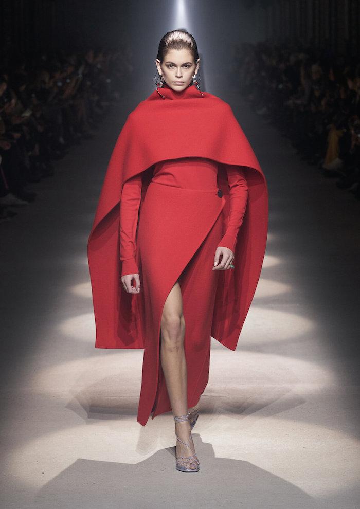 une robe asymetrique rouge kaia gerber sur le podium avec des sandales fines tenue chic femme