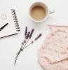 une table blanche avec quelques fleurs de lavande une tasse a cafe trcot et carnet