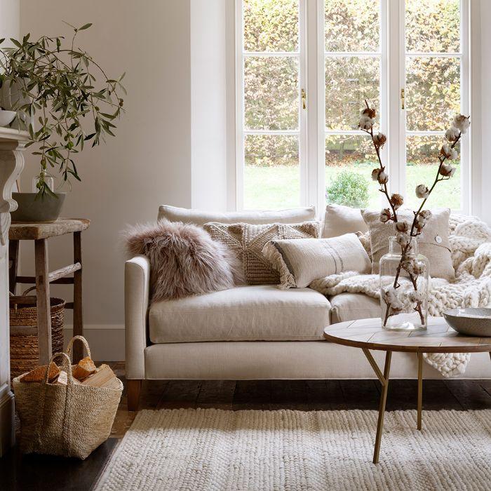 vase à branches de coton sur table minimaliste de bois tapis tricoté canapé blanc cassé décoré de plaid grossesmailles et coussins deco chic de salon