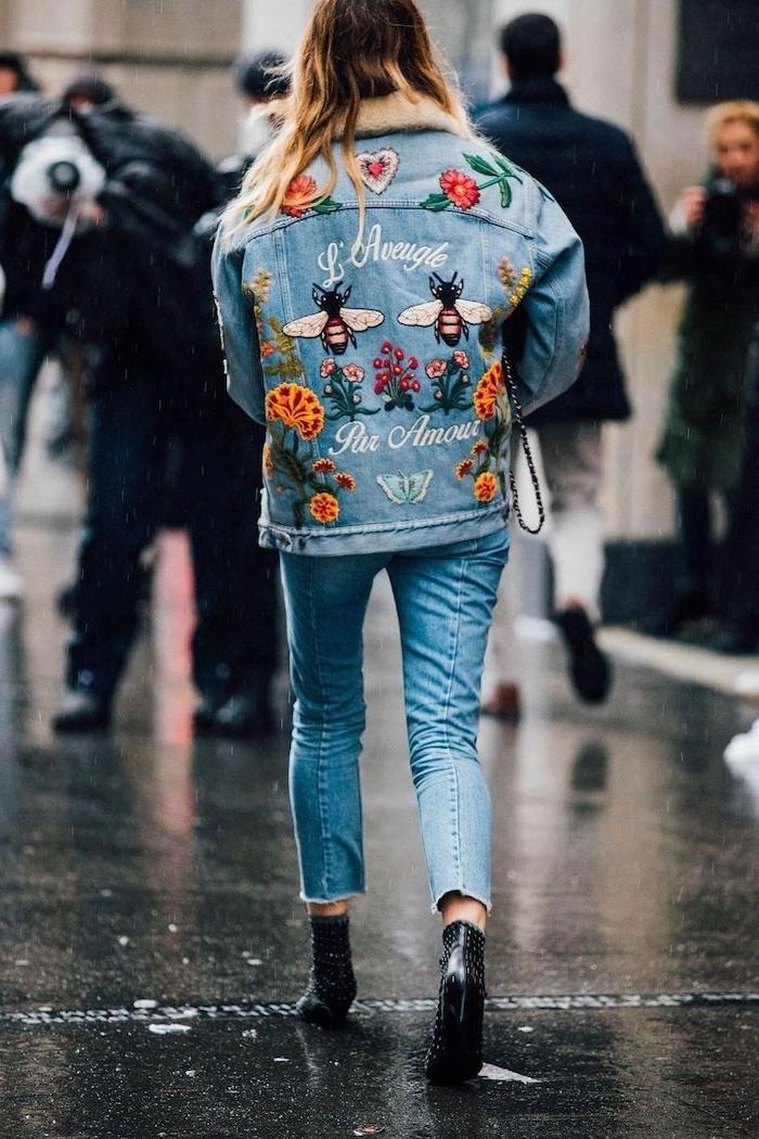 veste en jean customisee avec des applications et des ecritaux une femme toute en jean dans la rue avec des bottes noires
