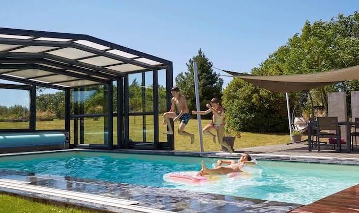 abri de piscine haut deux enfants qui se jetent dans la piscine un lit ballonne