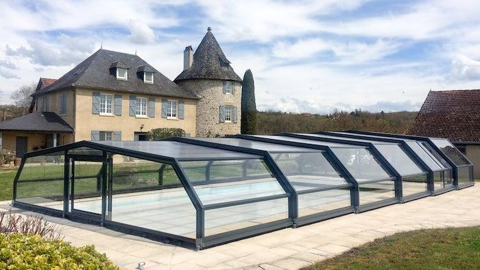 abri de piscine mi haut pres d un chateau en tuiles avec un toit aigu