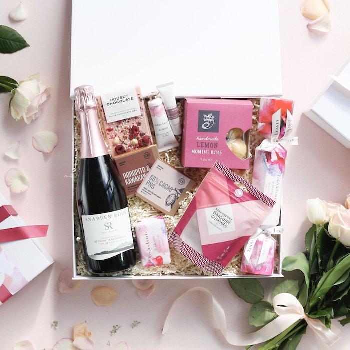 anniversaire en confinnement idee de cadeau une boite avec de champagne produits de beaute et un bouquet de roses