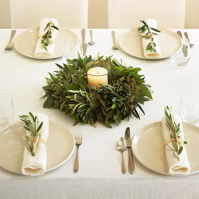 bougie blanche centre de table noel assiette blanche nappe couvercle table argent couronne verdure feuillage