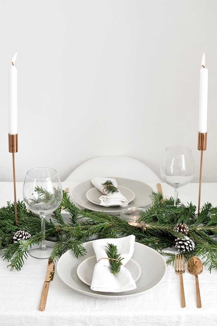 bougies blanches deco table noel nature bougeoir rose gold serviette blanche branches vertes verres pommes de pin blanches