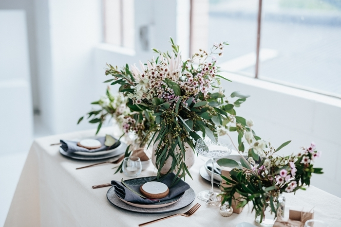 bouquet de plantes vertes herbe assiette ronde blanche serviette noire idee deco table noel couvercles laiton