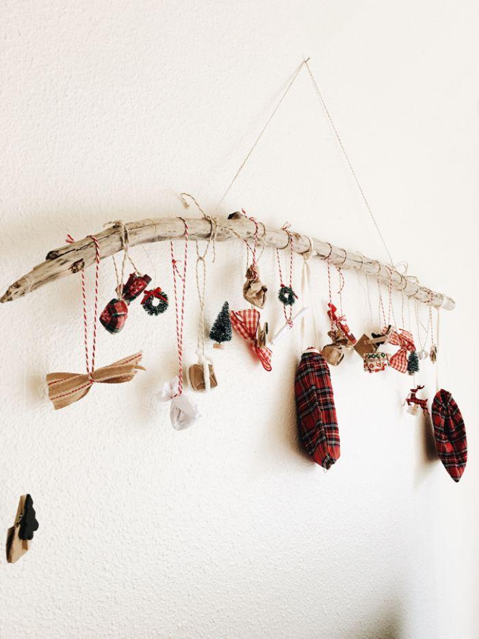 branche de bois avec des jouets suspendus sur des fils et petites décorations de noel figurines surprises