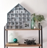 calendrier de l avent ado garcon avec une maison en bois decorative pose sur une etagere
