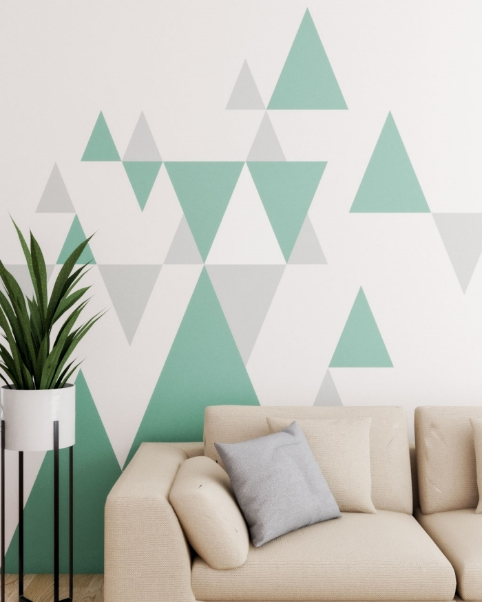 canapé beige peinture géométrique mur salon pot fleur blanc pieds métal formes peinture couleur gris nuances vert plante