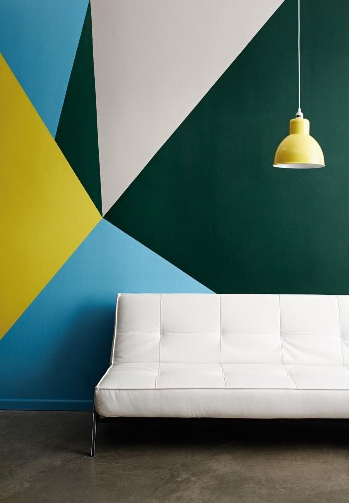 canapé blanc lampe suspendue jaune peinture géométrique mur salon formes triangulaires couleurs peinture vert foncé tendance