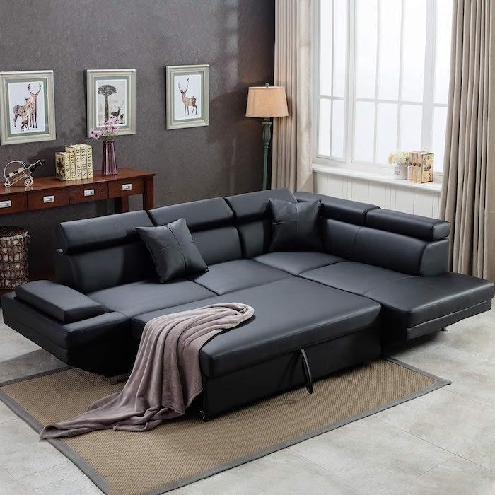 canapé d angle convertible en lit en cuir noir dans un salle de sejour avec des rideaux beiges et murs marron