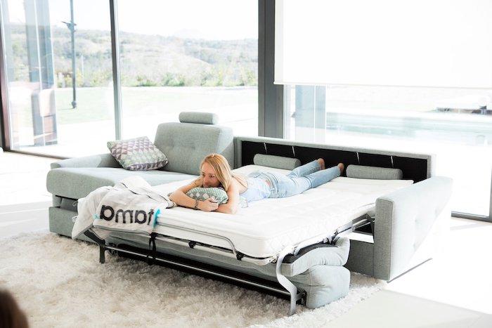 canapé d anlge convertible en lit avec un mecanisme stable devant une vitrine