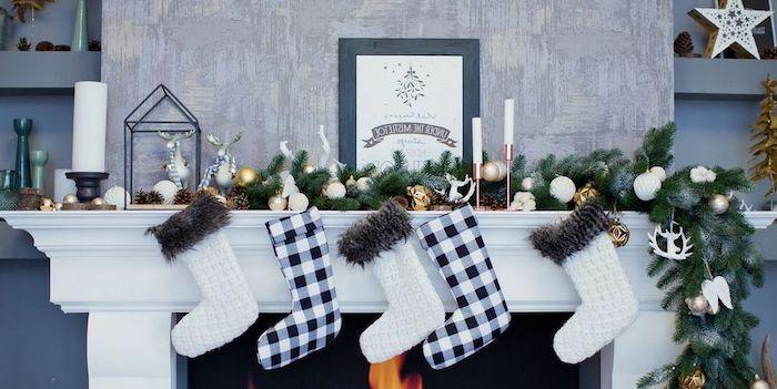 chaussette noel cheminée une décoration en thème blanc et bleu marin des chaussettes suspendus devant une guirlande