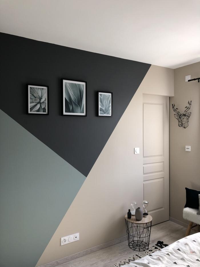 déco chambre moderne mur bicolore motifs géométriques peinture mur triangle table café bois et métal cadres photos noirs