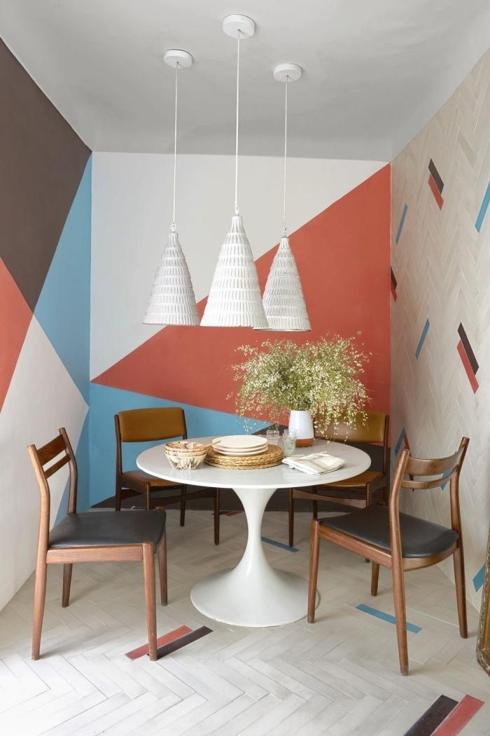décoration salle à manger petite table ronde blanche chaise bois peinture triangle couleur orange lampe suspendue
