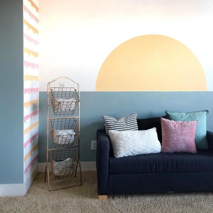 décoration salon mur bicolore idée motif peinture murale canapé noir coussins décoratifs peinture soleil meuble rangement panier