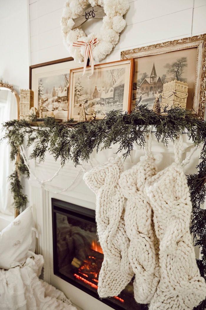 déco cheminée noel avec des guirlandes en verdure des chaussettes tricotes blancs et tableaux avec des cadres