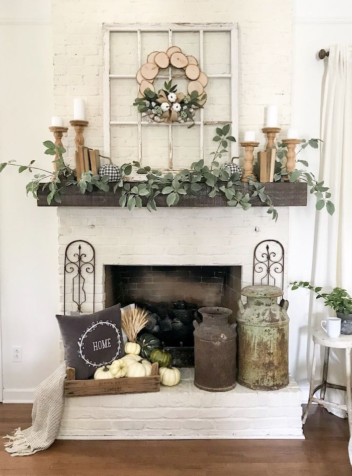 décoration de la cheminée avec de la verdure des vase vintages et une couronne en bois