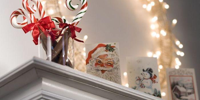deco cheminée noel avec des cartes festives et des batons en sucre devant une courronne de lumières