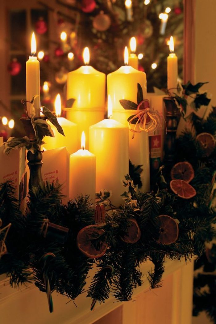 deco de noel avec des bougies de differentes dimmensions de la verdure et des rondes d orange secs
