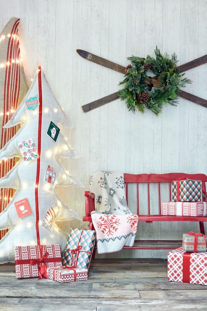deco de noel avec un sapin en carton des cadeau et un banc rouge des skis accroches au mur