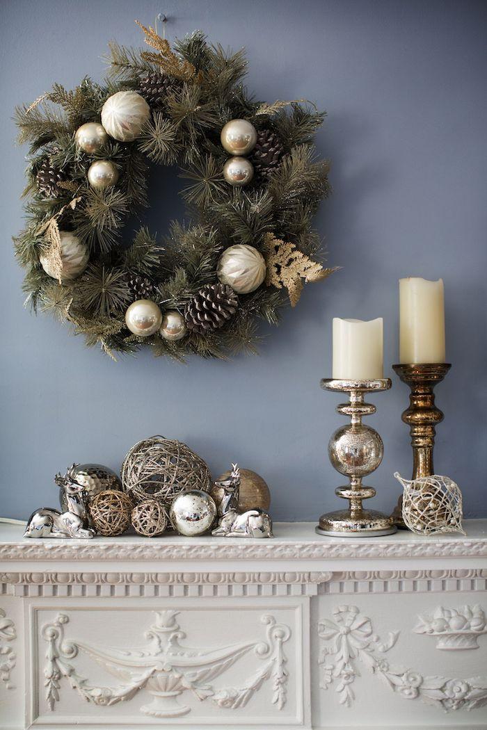deco fausse cheminée avec des jouettes bronzees une couronne a branches seches et des bougies dans bougeoir