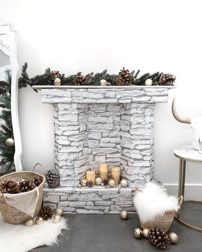 deco fausse cheminee en gris avec des bougies et une guirlandes des cones de pin