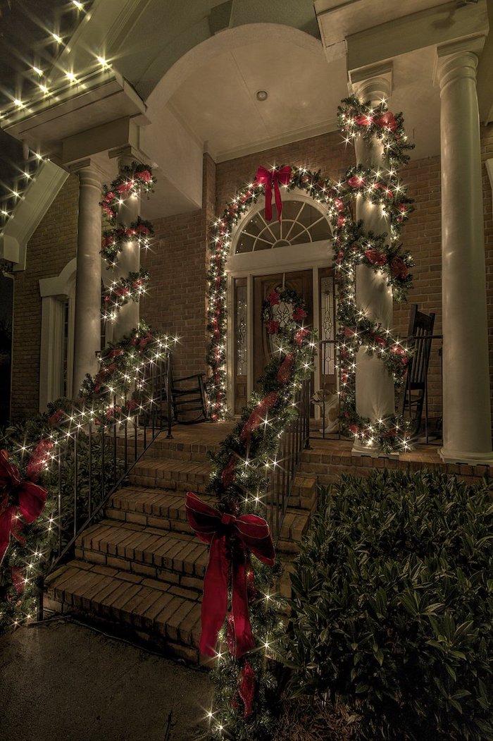 deco lumineuse avec des guirlandes vertes et des rubans rouges devant la maison