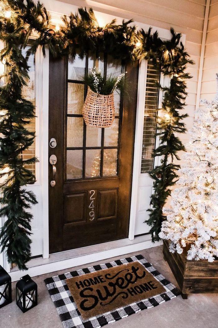 deco lumineuse devant la porte avec une guirlande noire et un sapin blanche un tapis avec message au sol