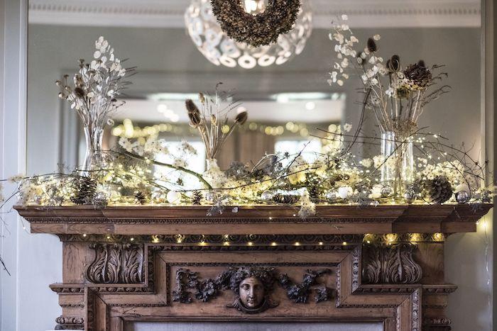 deco noel cheminée avec des petites lumières et deux vases un manteau luxueux avec des sculptures