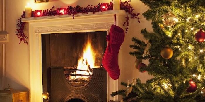 deco noel cheminee avec des fruits rouges et des boudies sur le manteau et un sapin vrai de cote