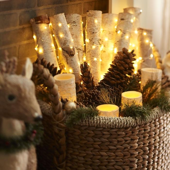 deco noel maison facile panier tressé rempli de bougies led guirlande lumineuse pommes de pin branches bois