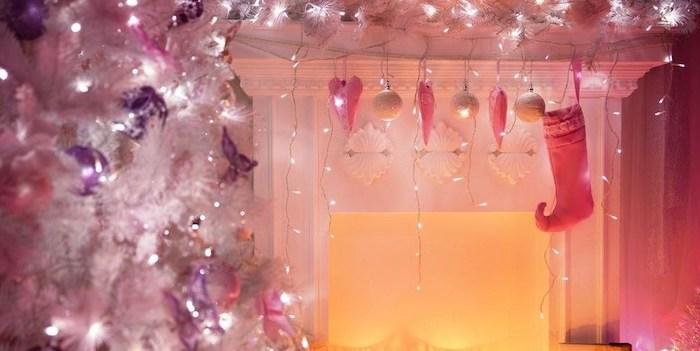 deco salon noel en rose avec un sapin blanc et des lumieres suspendus du manteau de la cheminee