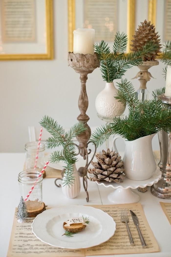deco table de noel avec matériaux nature pommes de pin bougeoirs branches de sapin rondelles bois couvercles argent