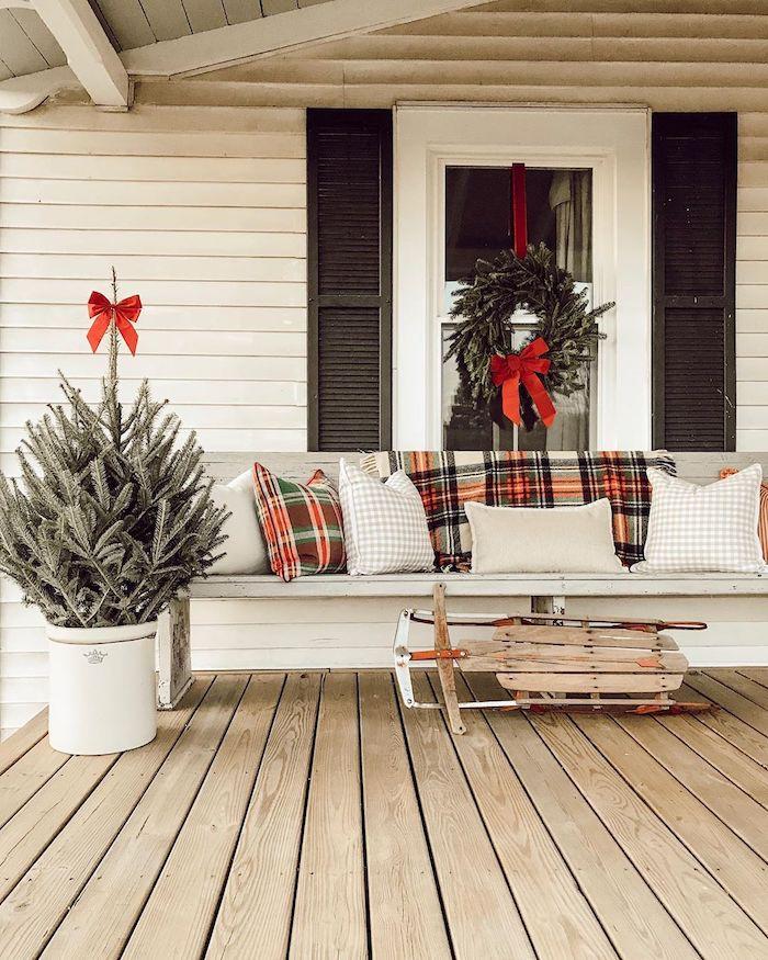 decoration dans le cour d avant dans un style rustique avec une luge et un sapin et des coussins en carreaux