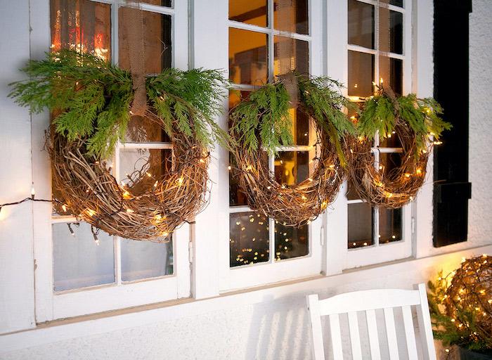 decoration de noel exterieur pas cher avec des courrones faits des vignes et des branches de sapin suspendus a la fenetre