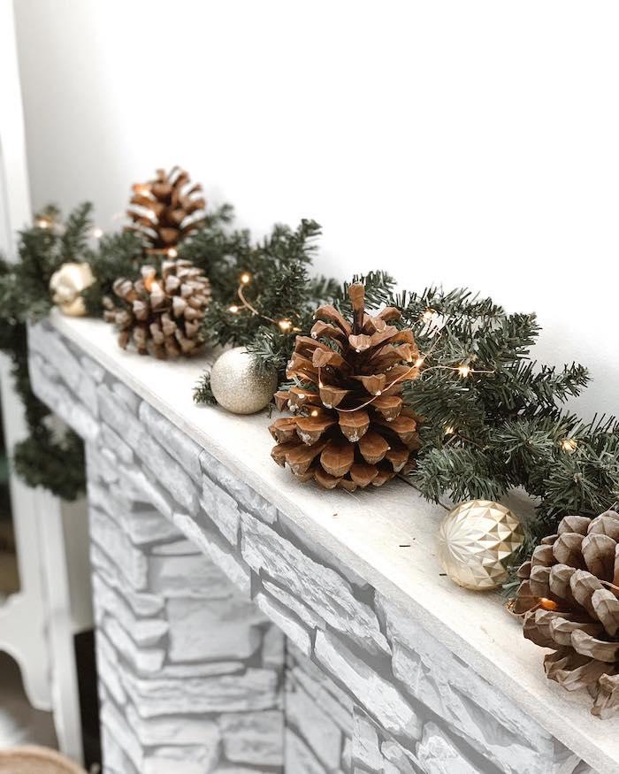 decoration de petites ornements sur le manteau de la cheminee avec des cones de pin et des petites balles